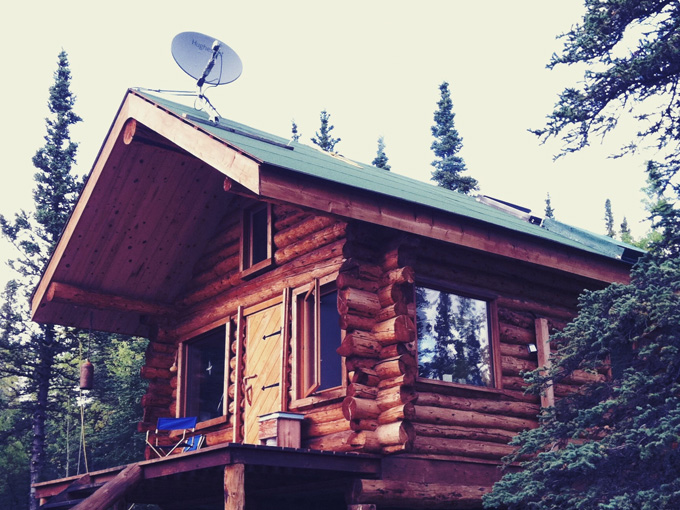 Cabin in Alaska with a satellite internet dish on the roof