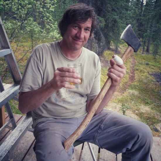 Photo of a guy with an axe, a bandaged thumb, and a glass of scotch
